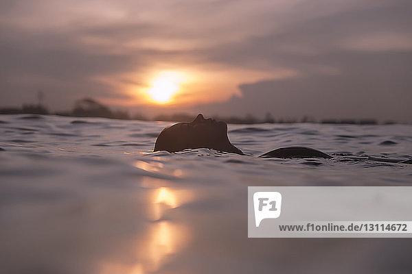 Unbeschwerte junge Frau schwimmt bei Sonnenuntergang im Meer gegen den Himmel