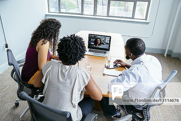 High angle view of business people discussing with businesswoman over video conference in board room