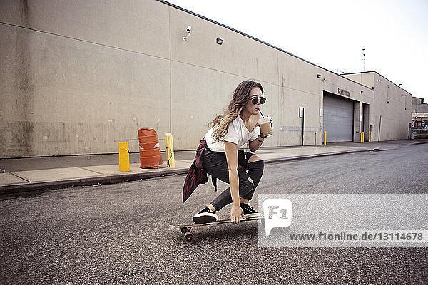 Frau trinkt Smoothie beim Skateboarden auf der Straße