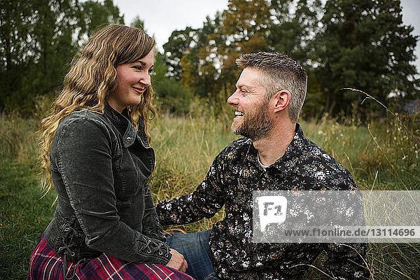Happy couple sitting on grassy field at farm