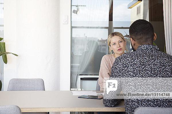 Geschäftsfrau diskutiert mit amtierendem Geschäftsmann