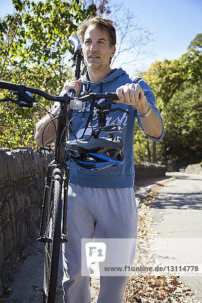 Man carrying bicycle on shoulder while walking on road