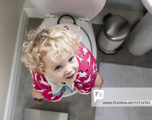 Portrait of happy girl sitting on toilet in bathroom