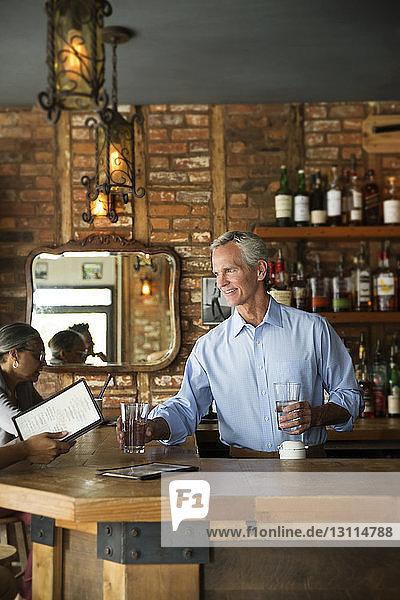 Selbstbewusster Besitzer serviert Kunden Getränke an der Bartheke im Café