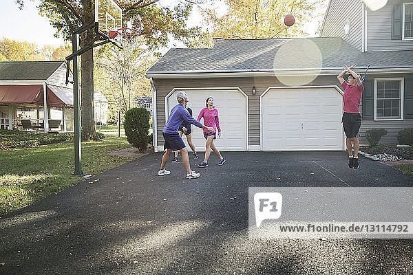 Family playing basketball at backyard on sunny day