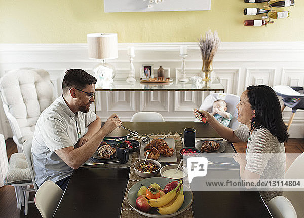 High angle view of parents having breakfast while sitting by daughter at dining table