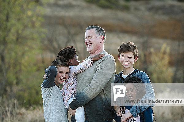 Glücklicher Vater mit im Wald stehenden Kindern