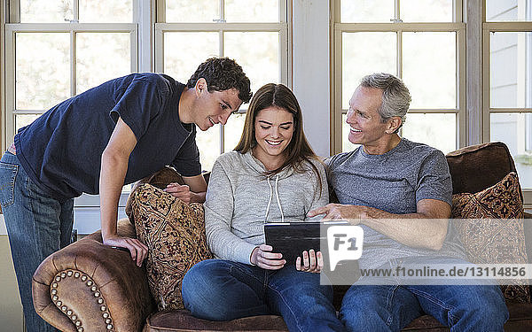 Happy family looking at tablet at home