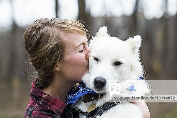 Seitenansicht einer glücklichen Frau  die einen Hund küsst Seitenansicht einer glücklichen Frau, die einen Hund küsst