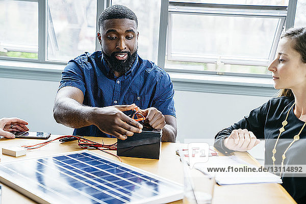 Geschäftsfrau betrachtet Kollegin  die im Büro Metallklammern an Batterie befestigt