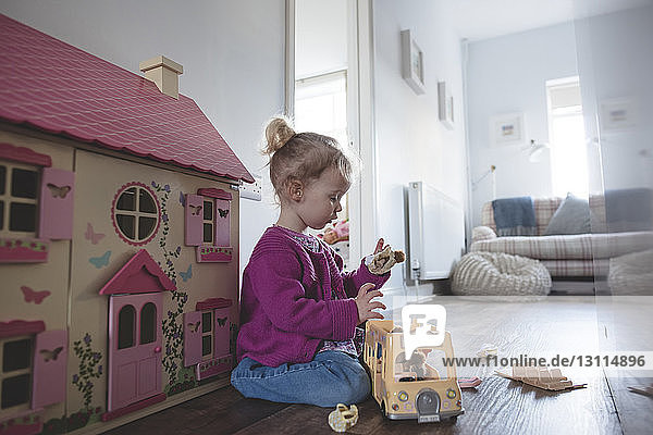 Side view of girl playing with toys at home