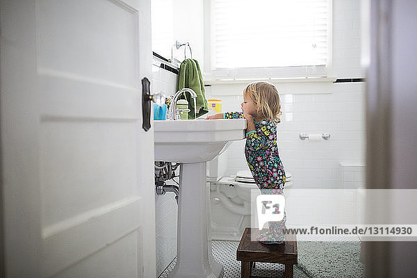 Side view of baby girl standing on stool by bathroom sink