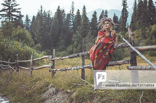 Nachdenkliche Frau  die einen Kranz trägt  während sie auf dem Feld steht