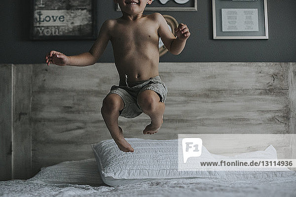 Playful shirtless boy jumping on bed at home