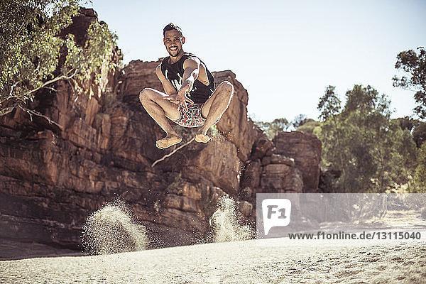 Porträt eines Mannes  der am sonnigen Tag in der Wüste auf Sand gegen den Himmel springt