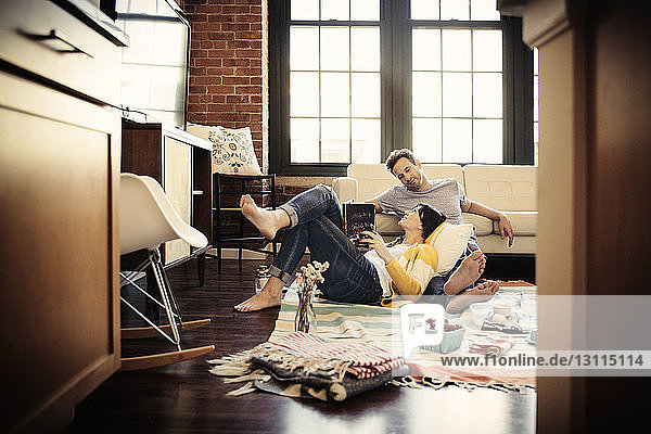 Smiling couple relaxing on carpet at home