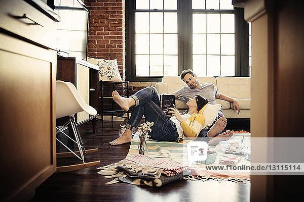 Lächelndes Paar entspannt zu Hause auf Teppich