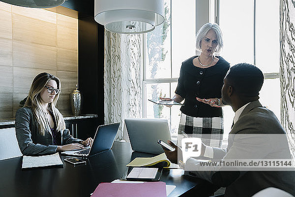 Businesswoman explaining to male colleagues during meeting in board room