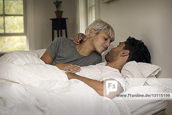 Liebevolles junges Paar,  das zu Hause im Bett liegt