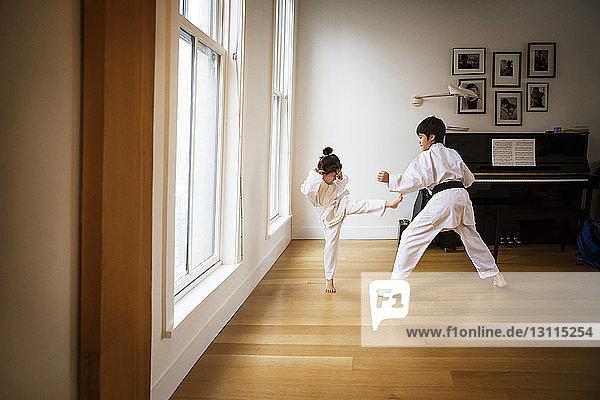 Geschwister üben zu Hause Karate am Fenster