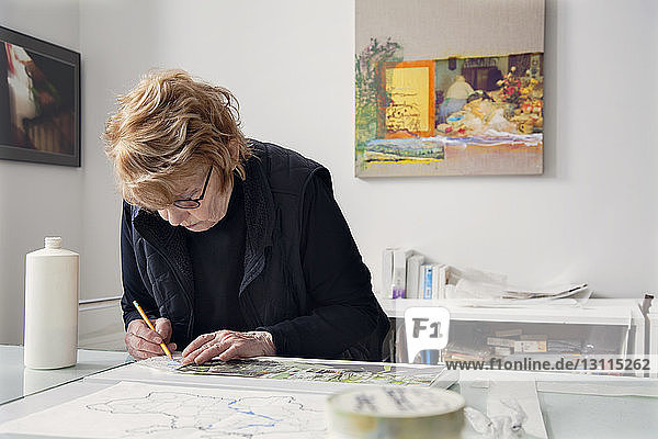 Senior female craftsperson drawing on table at home