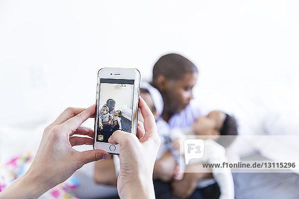Abgetrennte Hände einer Frau  die einen Mann mit kleinen Mädchen zu Hause fotografiert