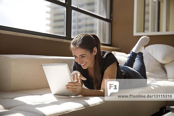 Lächelnde Frau benutzt digitales Tablet  während sie zu Hause auf dem Sofa liegt