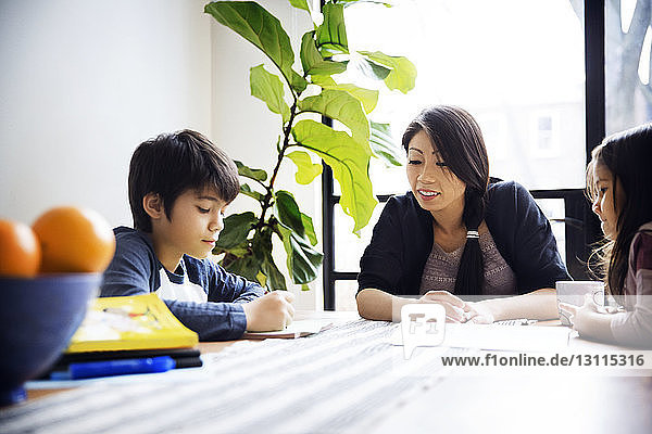 Mother teaching children on table at home