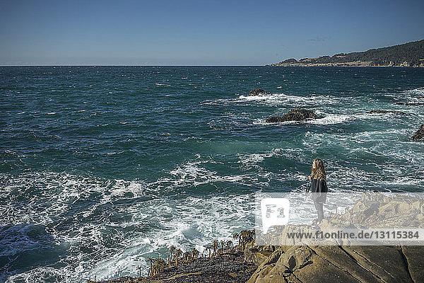 Hochwinkelaufnahme einer Frau  die auf Felsen am Strand vor klarem Himmel steht
