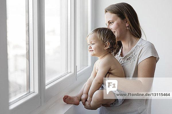 Seitenansicht einer Mutter  die eine Tochter trägt  während sie zu Hause durch ein Fenster schaut