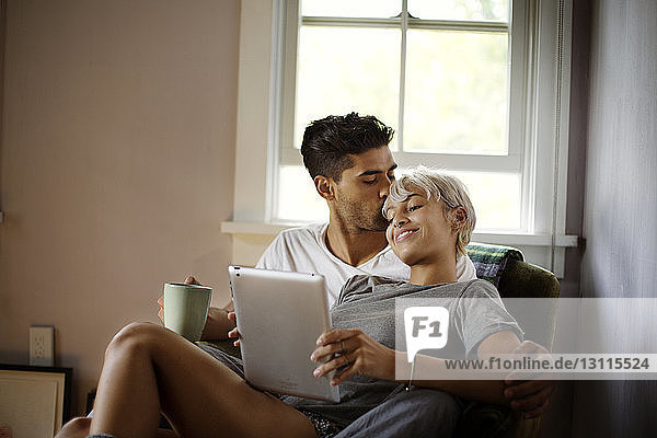 Man kissing woman using tablet computer at home