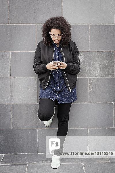 Junge Frau in voller Länge  die ein Smartphone benutzt  während sie sich an eine Betonwand lehnt