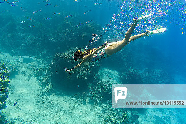 Frau beim Fotografieren im Meer