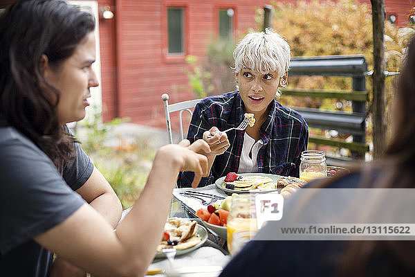 Young woman looking at friend while having breakfast