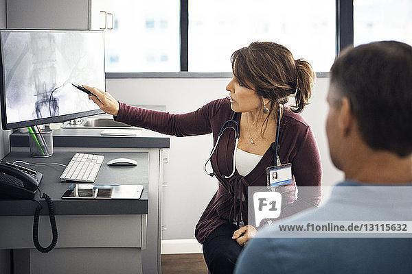 Ärztin erklärt dem Patienten den Bericht am Computer in der Klinik