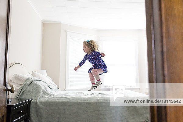 Side view of happy girl jumping on bed at home