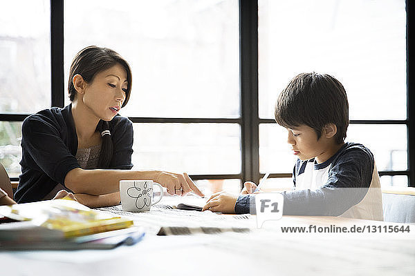 Mother assisting son in doing homework on table