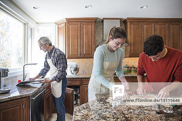 Family preparing gingerbread cookies in kitchen at home