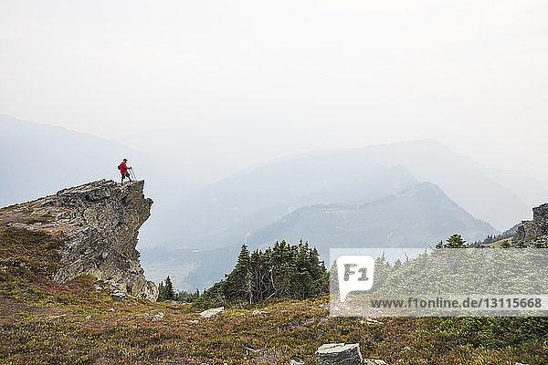 Wanderer in voller Länge auf Klippe stehend gegen Berge und Himmel bei Nebelwetter