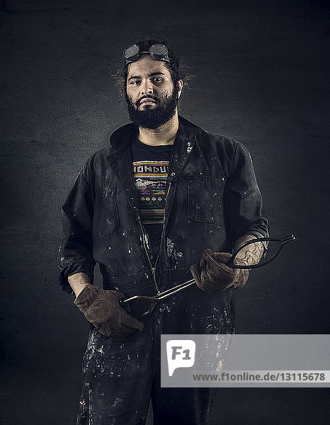 Portrait of confident craftsman holding tongs while standing against black background