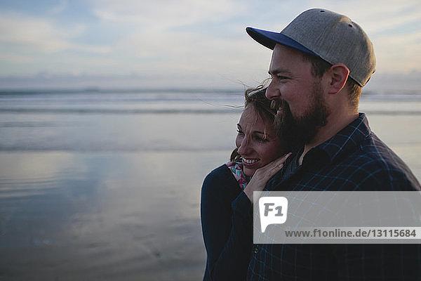 Fröhliches Paar steht am Strand gegen den Himmel