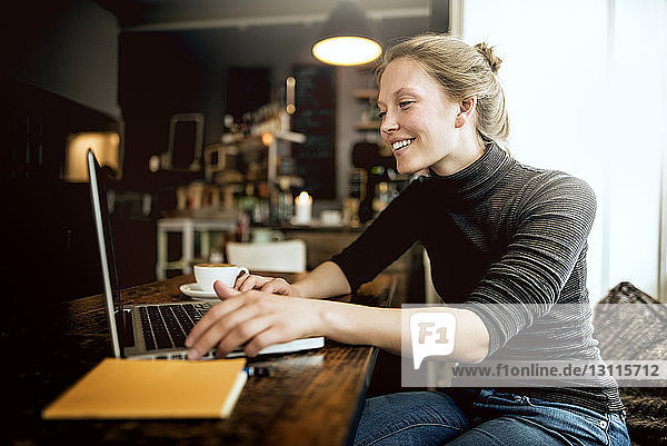 Happy young woman using laptop at cafe