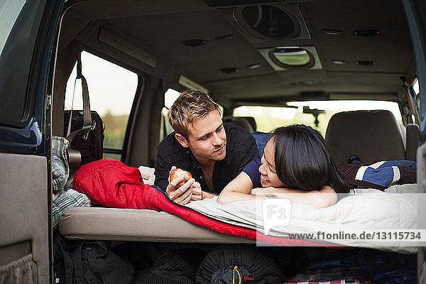 Couple lying in back of camping van