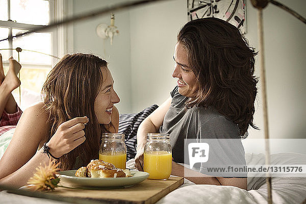 Happy couple having breakfast in bedroom