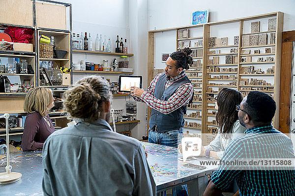 Geschäftsmann zeigt Kollegen im Büro Grafiken auf einem Tablet-Computer