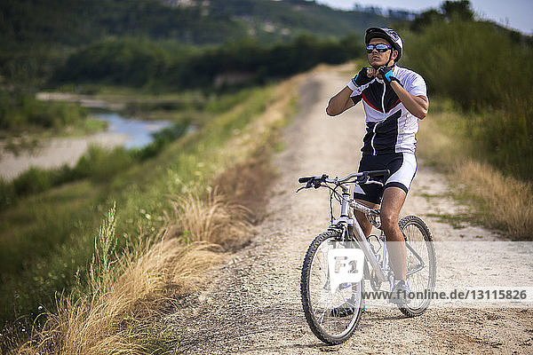 Cyclist fastening helmet while sitting on bicycle on dirt road