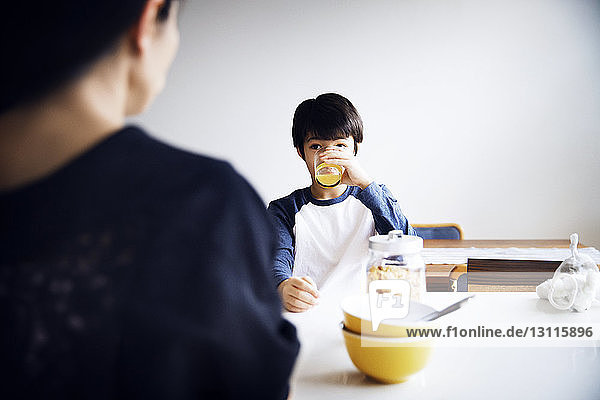Boy drinking juice while eating breakfast with mother at home