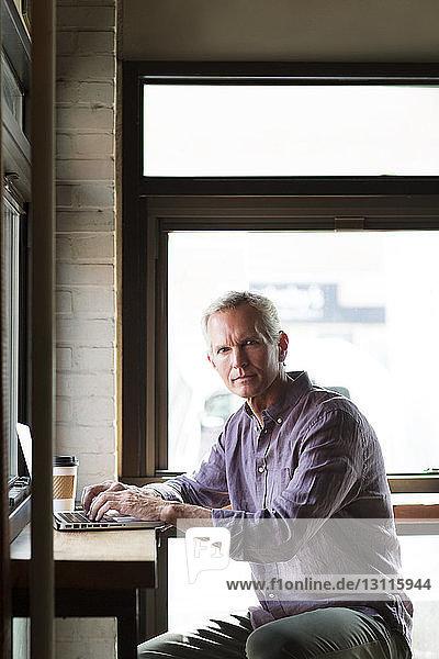 Porträt eines seriösen reifen Mannes mit Laptop am Tisch im Cafe