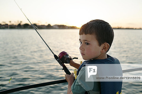Boy looking away while fishing on boat