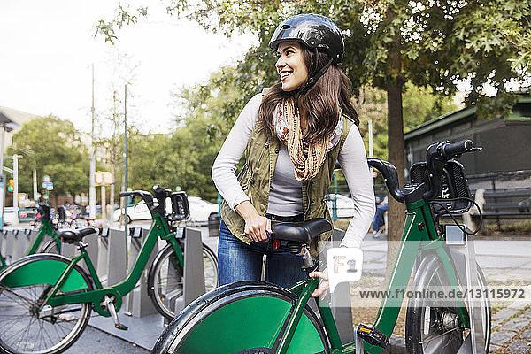 Glückliche Frau verstellt Fahrradsitz  während sie auf dem Parkplatz steht
